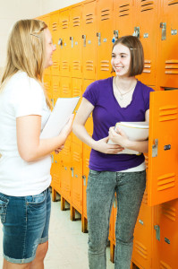 Two teenage girls chatting by their lockers in the school hallway.